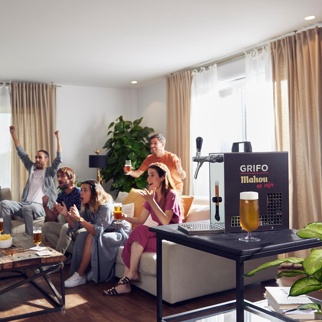 Gente disfrutando en casa de su grifo Mahou